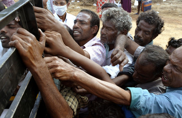 Indian tsunami survivors rush to collect food and clothing from a relief vehicle in a village in ...