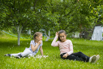 Little sister girls are playing with poplar fluff on the green park outdoor.
