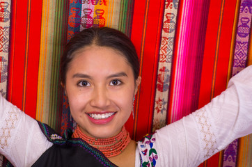 Closeup of a beautiful hispanic model wearing andean traditional clothing smiling and posing for camera, colorful fabrics background
