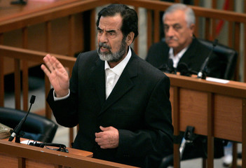 Former Iraqi leader Saddam gestures during the first day of his trial for genocide against Kurds in the 1980s in Baghdad