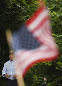 A member of audience waves a flag as Republican presidential candidate U.S. Senator McCain is introduced at a campaign picnic outside the Maine Military Museum in South Portland