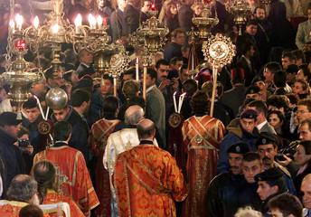 Russian Orthodox priests march with religious symbols through the crowds during the Christmas celebr..