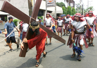 A Filipino penitent carries a 100 kilogram wooden cross on his shoulder while being whipped along a ..