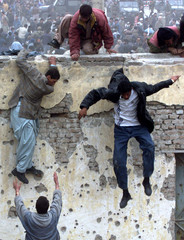 AFGHAN SOCCER FANS JUMPS OVER A STADIUM WALL IN KABUL.