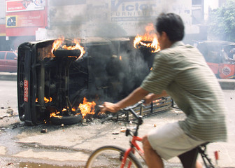 A MAN RIDES BY A BURNING VEHICLE IN JAKARTA.
