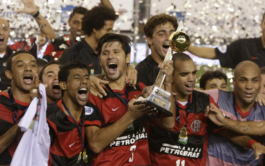 Flamengo's Luciano and team mates celebrate with trophy after winning Carioca Championships match against Botafogo in Rio de Janeiro