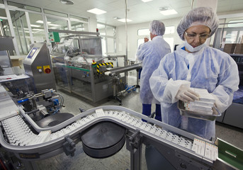 A worker collects packages of H1N1 flu vaccines from a conveyer belt at a plant in Burgos