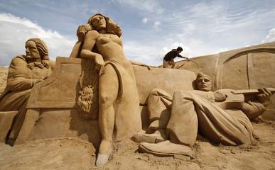 Artist works on his sculpture during Sand Sculpture Festival in Travemuende