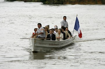 France's President Sarkozy and members of the government sit in a boat crossing the Oyapok river in Camopi