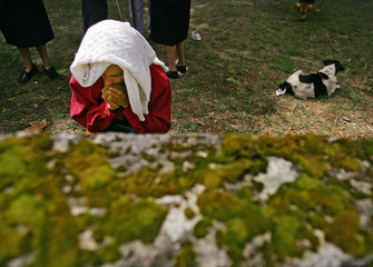 """Woman prays before the start of the annual """"Procession of the Shrouds"""" in north-western Spain."""