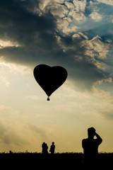 Silhouette of man tourist taking photos of heart shape hot air balloon at sunset