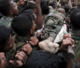 The body of LTTE leader Prabhakaran is carried on a stretcher through a group of Sri Lankan soldiers at Nanthikadal lagoon