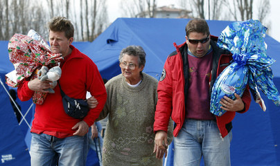 Two men holding easter eggs walk with their mother in an a tent camp where earthquake victims reside in Aquila