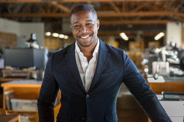 Charming successful smiling portrait of handsome african american professional in suit at office