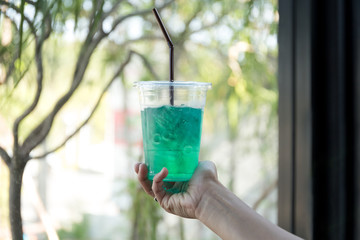 Hand holding healthy refreshment green drink