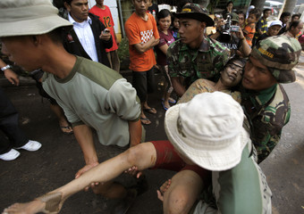 Members of a rescue team carry a survivor found at the site of a flooded housing complex on the outskirts of Jakarta