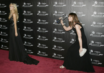 Actress Delta Goodrem and comedian Julia Zemiro pose on the red carpet at the Australian Film Institute Awards in Mlebourne