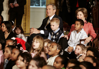 US President Bush sits alongside first lady Laura and children at a Christmas performance in Washington