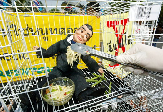 """A Greenpeace activist """"forcefeeds"""" a doll, representing humans, with a local salad made from genetic.."""