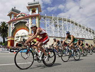 Competitors in the men's triathlon cycle past an amusement park at the Commonwealth Games in Melbourne