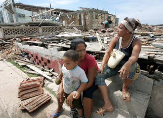 Cuban sisters sit with child on stairs of their destroyed home after Hurricane Charley passed over.