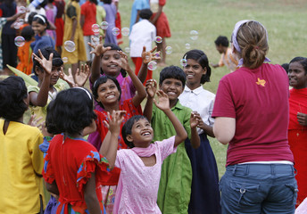 Seventh-day Adventist Church volunteer Dryer of the U.S. blows bubbles on the outskirts of Jeypore village