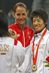 Pitchers Yukiko Ueno of Japan and Cat Osterman of the U.S. pose for a photo after the medal ceremony for the softball competition at the Beijing 2008 Olympic Games