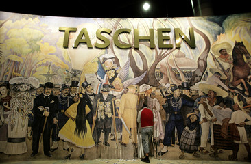 Workers prepare the background painting in the exhibition booth of German publishing house Taschen ahead of the Frankfurt book fair