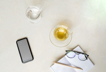 Top view cup of tea with cell phone, glass of water and glasses with pencil