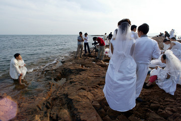 CHINESE NEWLYWEDS CROWD A SCENIC SPOT ON THE SEASIDE OF QINGDAO.