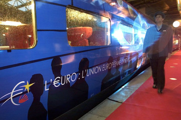 A TRAIN CONDUCTOR WALKS ALONGSIDE A HIGH-SPEED TRAIN EMBLAZONEDWITH THE SYMBOL OF THE EURO IN BRUSSELS.