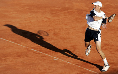 Davydenko of Russia returns the ball to Muller of Luxembourg during Estoril Open tennis tournament in Lisbon
