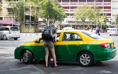 Tourist woman with backpack talking to taxi driver