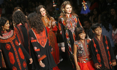 """Ismail and Ali of """"Slumdog Millionaire"""" display outfits designed by Ashima Leena during a fashion show on the second day of India Fashion Week in New Delhi"""