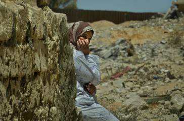 PALESTINIAN WOMAN SITS NEXT HER DAMAGED HOUSE AT THE RAFAH REFUGEE CAMP.