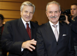 European Central Bank President Trichet walks with Roth Swiss National Bank President before a conference in Lausanne