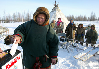 NENETS MAN DROPS HIS BALLOT AS HE VOTES AT MOBILE POLLING STATION NEAR THE VILLAGE YAR-SALE.
