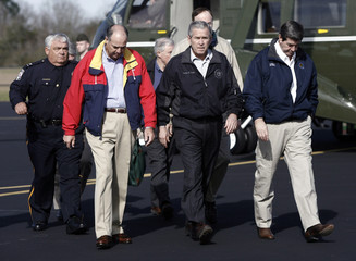 U.S. President Bush walks with Alabama Governor Riley and Enterprise Mayor Boswell in Alabama