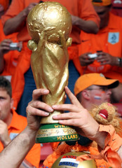A replica of the World Cup trophy is lifted in the stands in Stuttgart