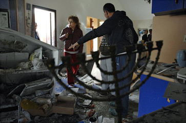 Israelis survey the damage in their house after a rocket landed in Sderot