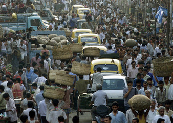 CARS AND PEOPLE MOVE THROUGH A BUSY STREET IN CALCUTTA.