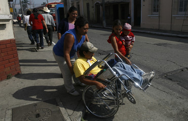 Jorge Choy, 23, a former driver who was wounded last year during an attack on his bus, is wheeled to the Human Rights Ombudsman's office in Guatemala City