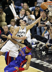 Spurs' Ginobili goes up for a basket between Pistons's Prince and Wallace during second half play in ...
