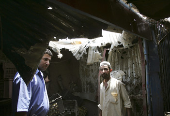 A policeman and a resident stand under a hole on a roof created by a mortar attack in a crowded market in Baghdad