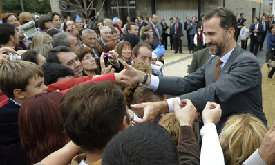 Spain's Crown Prince Felipe greets the crowd during a visit to village of Sobrescobio