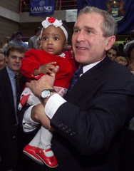 BUSH HOLDS A YOUNG GIRL AT RALLY IN MICHIGAN.