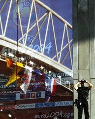A PORTUGUESE POLICEMAN STANDS NEAR EURO 2004 LOGO REFLECTED IN A GLASS WALL AS HE STANDS GUARD ...