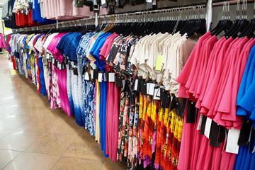 Different dresses on hangers in store