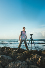 a young man stands on the coast, and photographing nature with the camera on a tripod