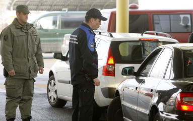 Customs officers control a car at the Swiss-German border crossing in the town of Thayngen